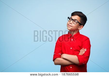 Adorable young man standing with arms crossed and daydreaming on the blue background.