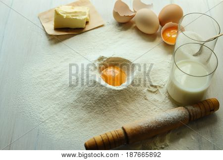 Eggs flour milk sugar oil on a white wooden table. Preparation of ingredients for baking.