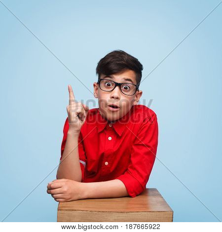 Young amazed boy in red shirt pointing up on the blue background.