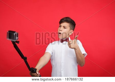 Young teen vlogger showing thumb up gesture while filming a video.