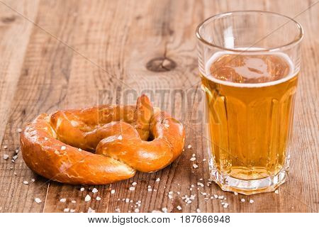 Bavarian pretzel with beer glass on wooden table.