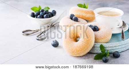 Doughnuts with powdered sugar, cup coffee and fresh blueberries on light gray background. Selective focus. Copy space.