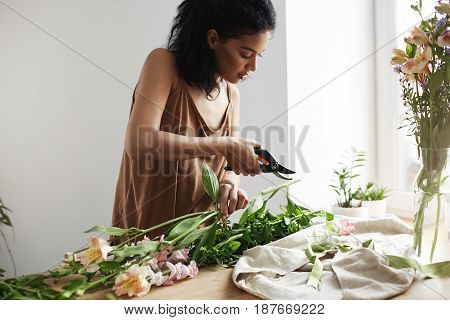 Young attractive african female florist cutting flower stems at workplace. White wall background.