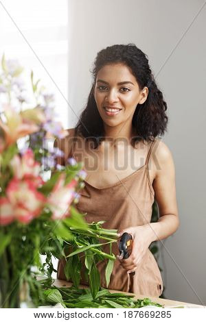 Portrait of beautiful african girl florist smiling looking at camera making flowers bouquet. White background.