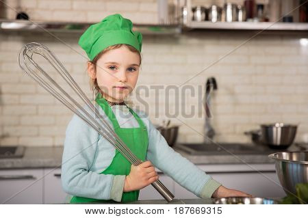 Little girl in chef hat with whish on the kitchen