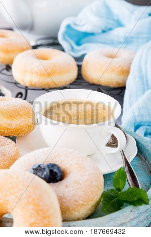 Cup of coffee and homemade donuts with powdered sugar and fresh blueberries on light gray background. Selective focus.