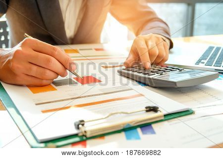 Businessman analyzes graph data and use the calculator to calculate the cost.