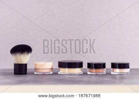 Mineral cosmetics beauty makeup powder kit with kabuki brush on gray. Copyspace