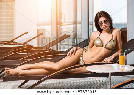 Young attractive slim girl in bikini relaxing on deck chair in wellness spa hotel resort. Near the table is a glass of orange juice. sun flare