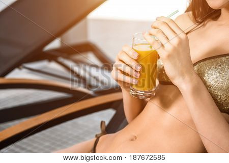 Young attractive slim girl in bikini relaxing on deck chair in wellness spa hotel resort. Woman holding a glass of orange juice. sun flare