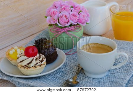 Cup of tea with milk cute sweet cake orange juice on wooden background. Good morning surprise concept.