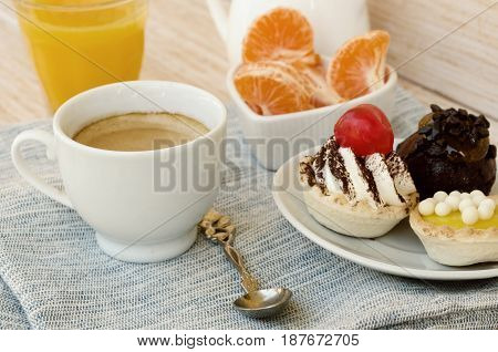 Cup of tea with milk cute sweet cake orange juice and fruit on wooden background. Good morning surprise concept.  Vintage filter.