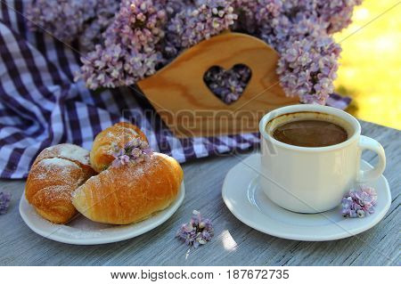 Cup of coffee with croissants and a bouquet of lilacs