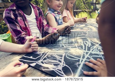 Group of kindergarten kids friends drawing art class outdoors