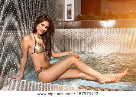Beautiful young woman in bikini sitting on the edge of the swimming pool. Jacuzzi. Resort. sun flare
