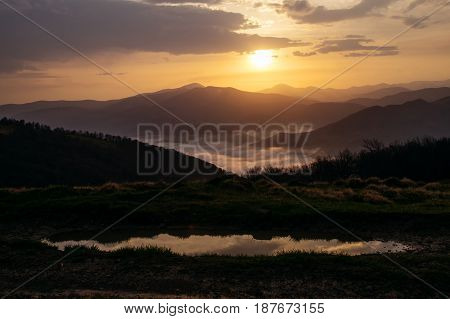 Beautiful mountain landscape. Colorful dawn in the mountains with a haze at the foot of the mountains and reflection in a puddle.