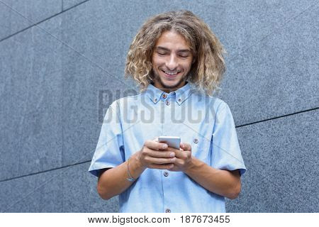 Gadget addiction, global communications concept. Young smiling man using smartphone - chatting in social networks with smartphone outdoor, copy space foe text
