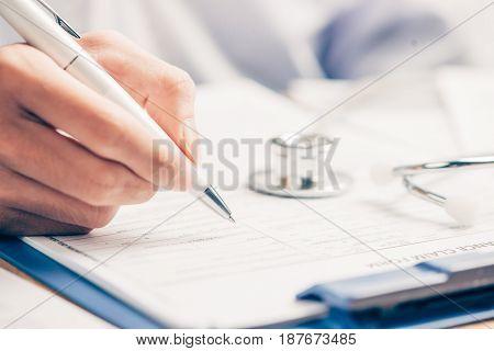 Female doctor filling medical form on clipboard