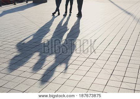 Shadows of three friends on pavement. Silhouettes of group of people, walking on stone roadway, copy space