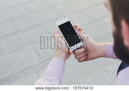 Man using smartphone with blank screen, mockup. Top view on unrecognizable guy reading information in mobile phone, copy space for advertisement.