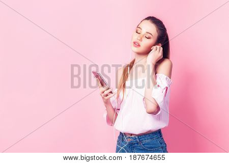 Beautiful young teenage girl in headphones listening to music with closed eyes standing on a pink background