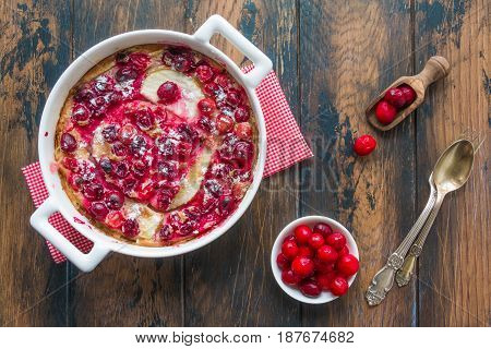 Homemade French tart clafoutis with frozen cranberries pears and flan-like batter in a white baking dish and berries on the rustic wooden table top view.