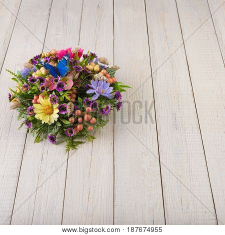 Colorful composition made of artificial flowers, fruits, butterflies, birds and ears of wheat in stylish vase on white wooden background.