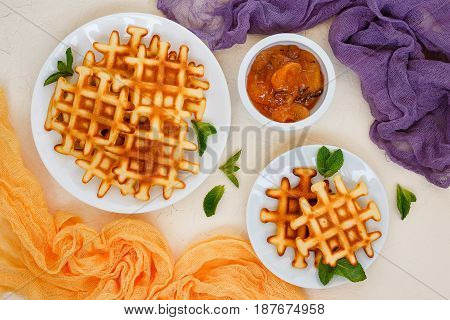 Two plates of Belgian waffles garnished with mint leaves and peach Jam with rosemary in small bowl. Top view.