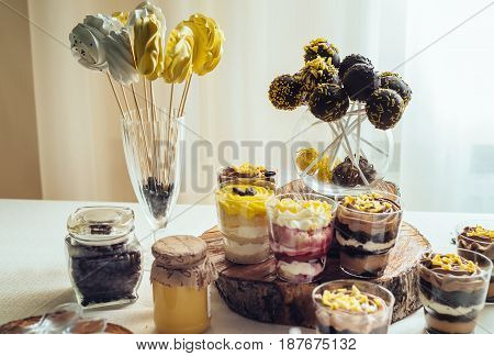 Meringues On Stick In Glass With Coffee Beans. Holiday Candy Bar In Yellow And Brown Color. Wedding