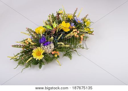 Colorful composition made of artificial flowers, fruits, butterflies, birds and ears of wheat in stylish vase on white background.