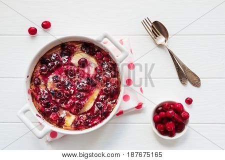 French fruit dessert clafoutis with cranberries and pears in white baking dish and berries on the wooden table top view.