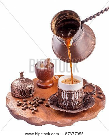 Traditional turkish coffee pouring isolated on white. Embossed metal cup and cezve.