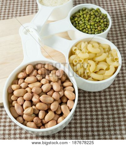 Foods High in Carbohydrate Raw Pasta Rice Peanuts and Mung Beans in Plastic Measuring Spoons.
