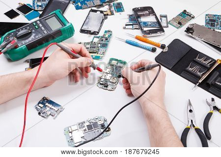 Repairing smartphone with multimeter close up. Technician pov, broken phone diagnostic at service center, repairman workplace