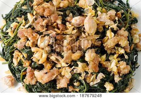 Chinese Traditional Food Close Up of Stir Fried Jute Leaves or Mulukhiyah Leaves with Minced Pork Garlics and Fermented Soy Bean.