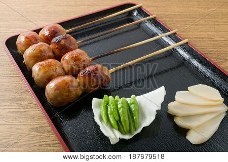 Food and Cuisine Plate of Thai Grilled Sausages on Wooden Skewer Served with Pickled Ginger Cabbage and Chili Pepper.