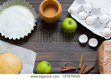 Pie with apple and berry jam on a dark wooden background