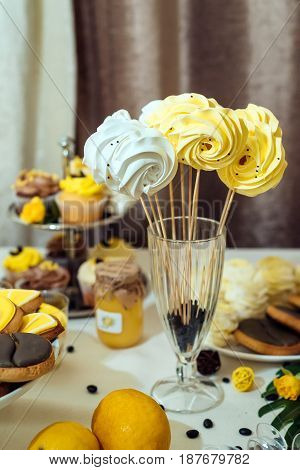 White and yellow meringues on stick in glass with coffee beans. Holiday candy bar in yellow and brown color. Wedding candy bar