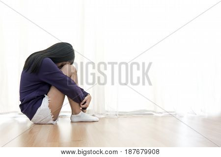Sad young woman sit in her room and covering her face after domestic violence