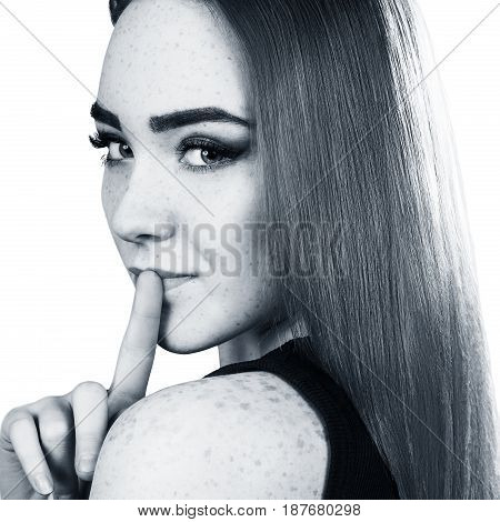 Beautiful girl holds finger near mouth. Womam shows silence gesture.