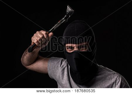 Criminal in T-shirt and balaclava with hammer. On black background at the studio. Bandit and thief