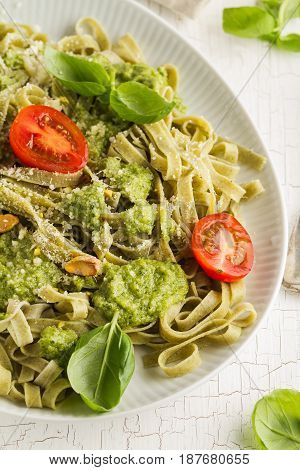 Tasty appetizing italian pasta with sauce pesto tomatoes and pistachios on white plate. Closeup.