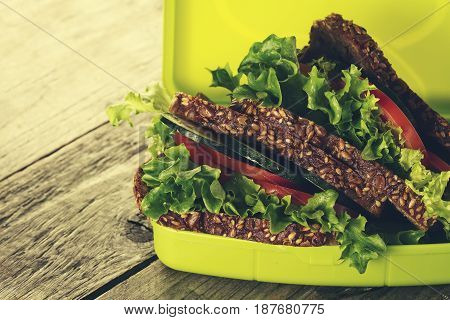 Tasty Healthy Vegetarian Vegan Sandwich in Lunch Box on Wooden Table Background. Horizontal. Copy Space. Closeup.