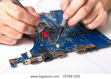 Laptop motherboard testing in service center close-up. Diagnostics of broken computer, electronics repair shop concept