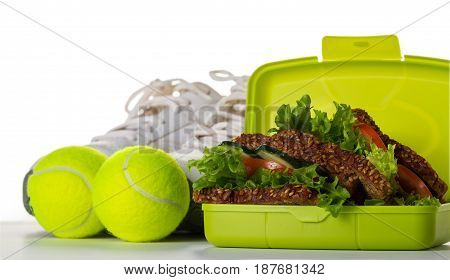Healthy Life Sport Concept. Sneakers with Tennis Balls Towel Apples Healthy Sandwich and Bottle of Water on Bright Background. Copy Space.