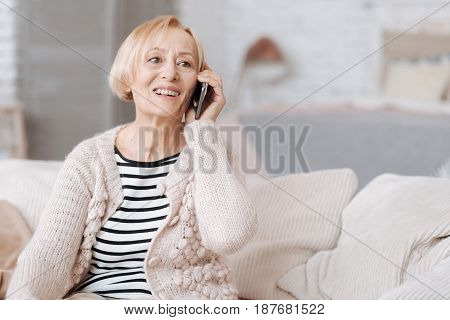 Nice hearing you. Friendly good looking nice woman using her phone for talking to somebody while sitting on a couch