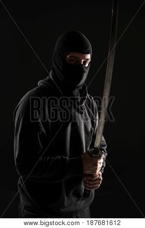 Man with balaclava and katana sword on black background at the studio. Criminal. Bandit and thief