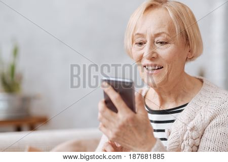 Keeping up with time. Smiling friendly aged lady holding her smartphone in her hands and typing something while spending time at home