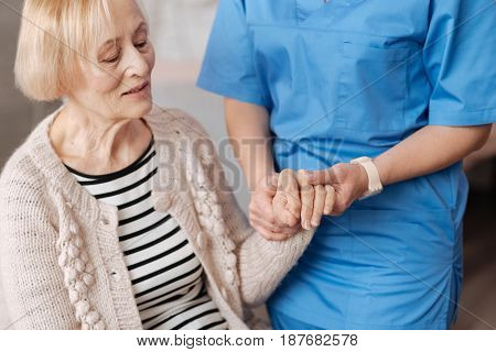 Regular checkup. Elderly frail cute woman sitting on a sofa at home and undergoing a general examination while experiencing some health issues