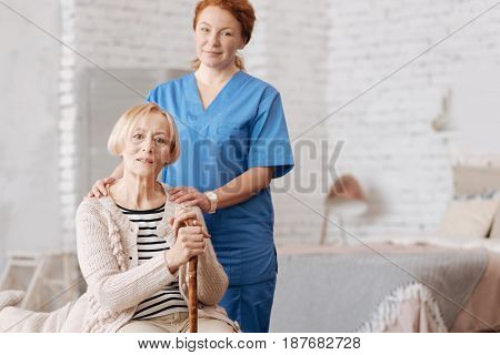 Home consultation. Skillful caring competent woman conducting a visit to the lady who being very old and worrying about her health